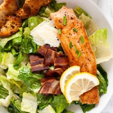a birds eye view of a bowl of salmon caesar salad