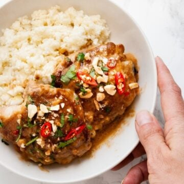 a hand holding a bowl of thai peanut chicken with cauliflower rice