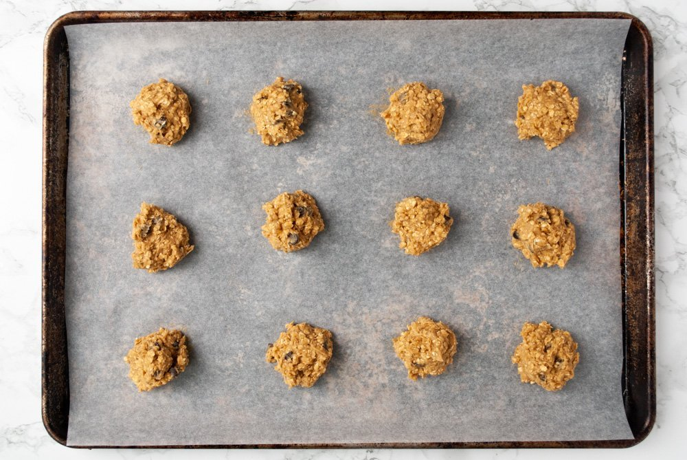a baking tray with unbaked balls of chewy oatmeal chocolate chip cookies