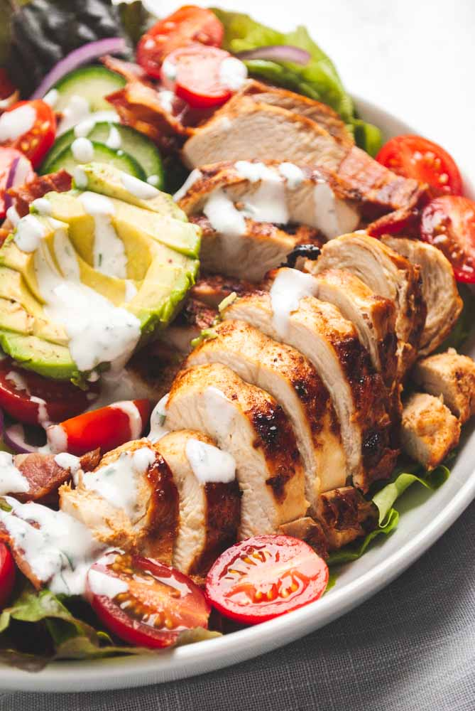 a close up view of sliced chicken on chicken bacon ranch salad