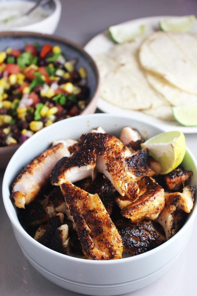 blackened fish and a bowl of black bean and corn salsa