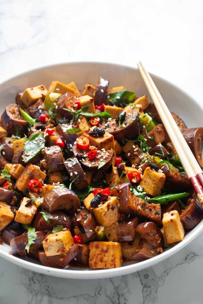 a serving bowl filled with spicy black bean tofu and eggplant