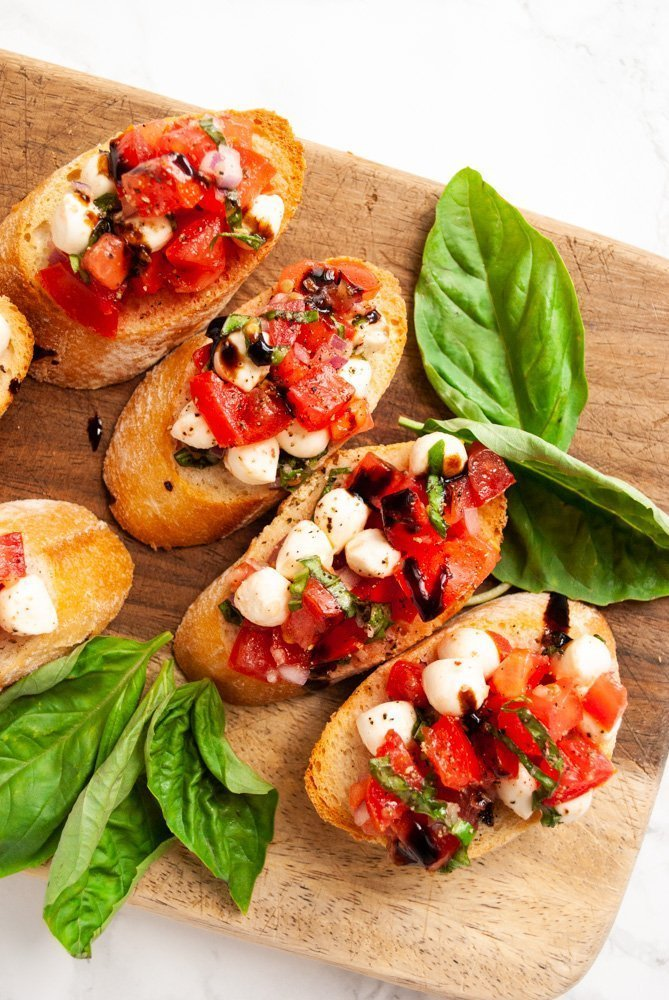 slices of bruschetta with mozzarella on a cutting board with fresh basil leaves