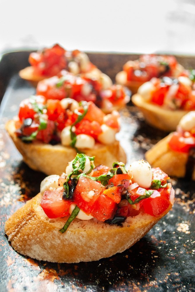 several pieces of bruschetta with mozzarella on a baking sheet