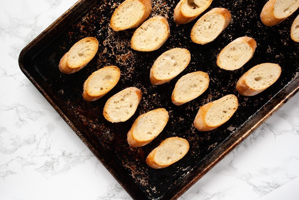 a baking tray topped with freshly toasted crostini