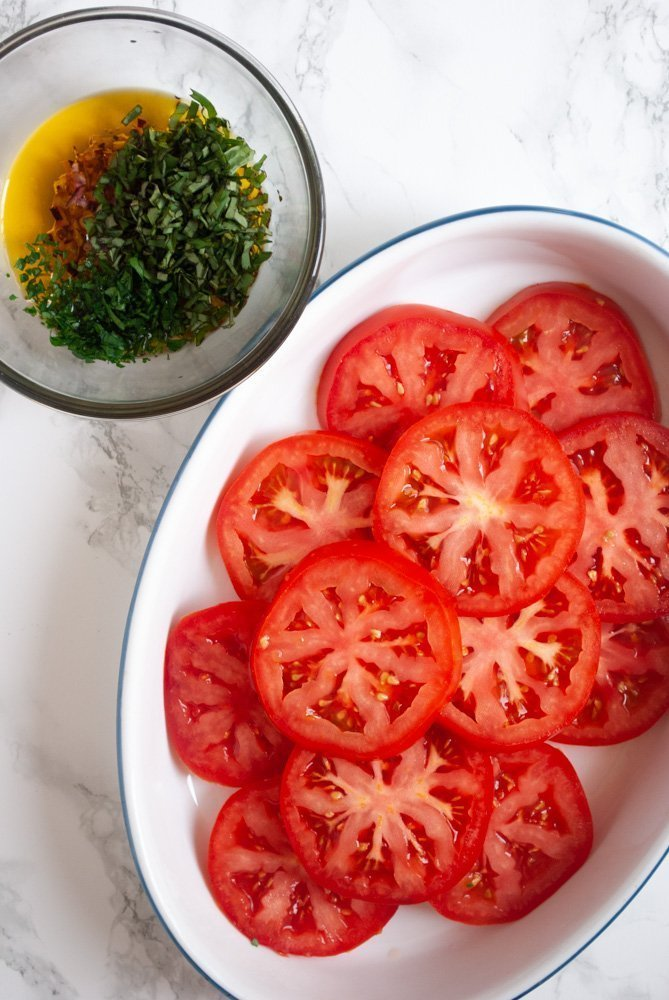 a plate of sliced beefsteak tomatoes next to a bowl of herb marinade