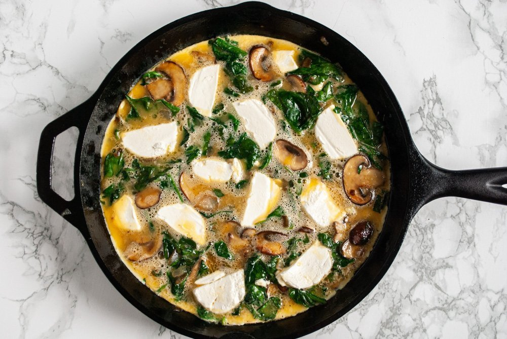 half cooked spinach and mushroom frittata with goat cheese in a skillet