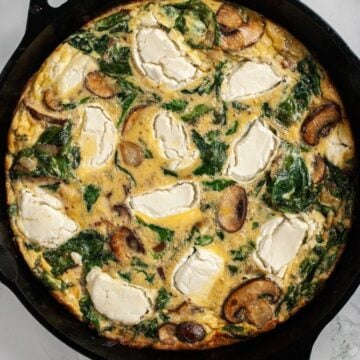 spinach and mushroom frittata with goat cheese freshly cooked in a cast iron skillet