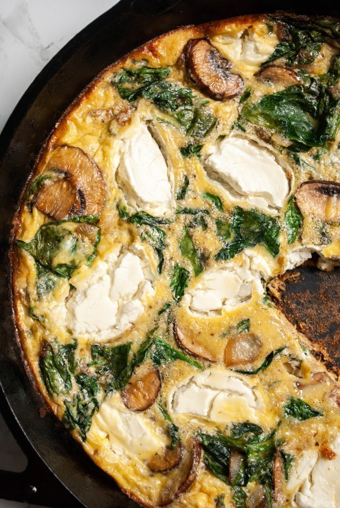 a close up of spinach and mushroom frittata with goat cheese