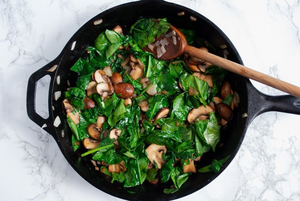 cooked onions, mushrooms and spinach in a skillet