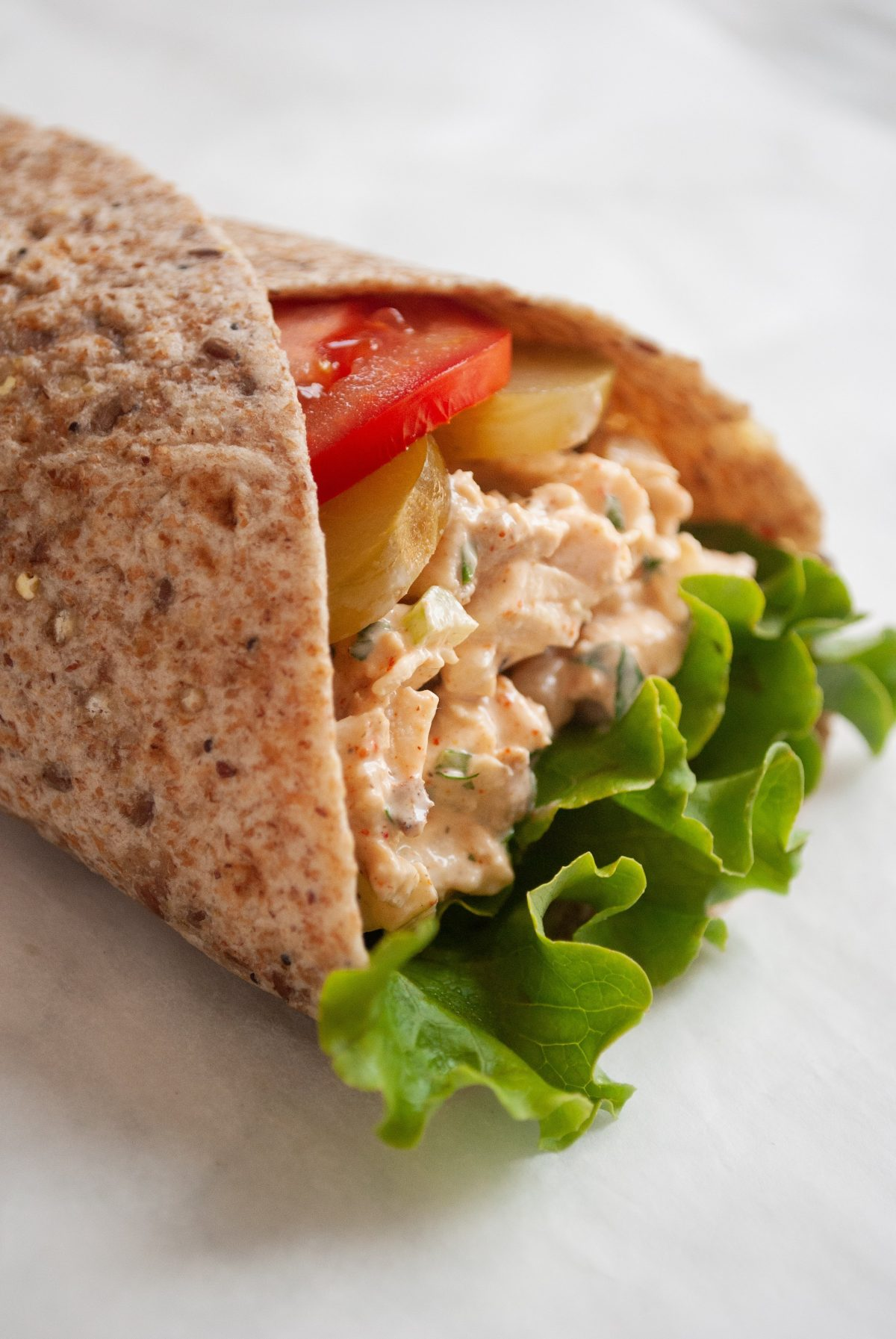 piri piri chicken salad with lettuce, tomato and pickle in a whole wheat wrap