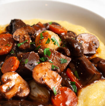a bowl of mushroom bourgignon on polenta