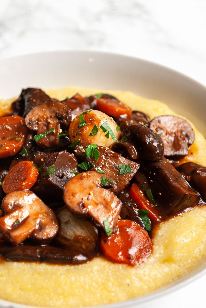 a bowl of mushroom bourguignon on polenta