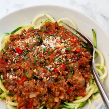 a bowl of sausage ragu over zucchini noodles