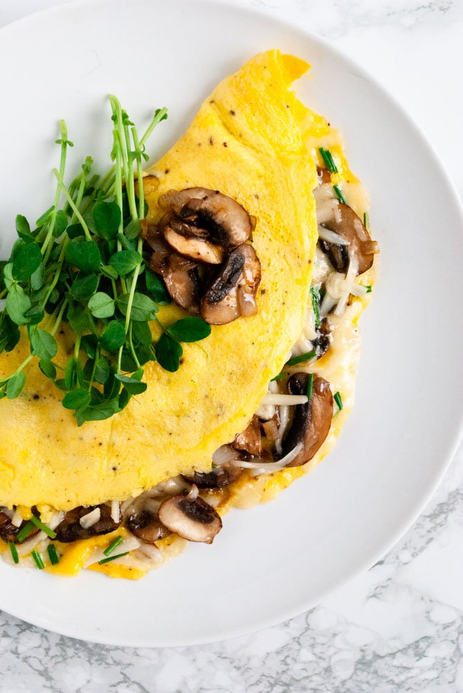 a mushroom omelette topped with micro greens