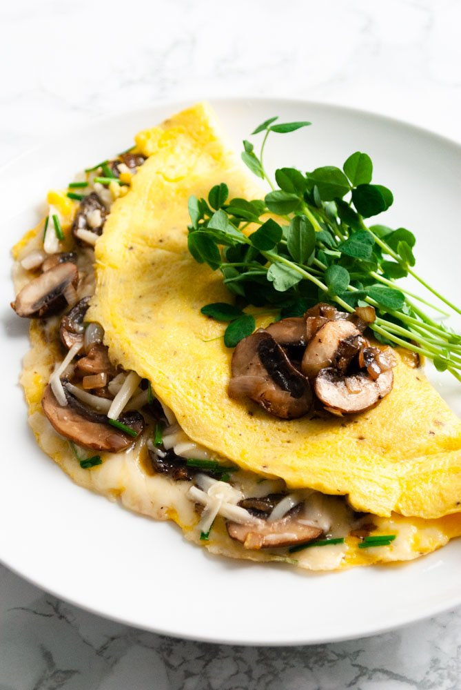 a mushroom and gruyere cheese omelette on a plate with pea shoots
