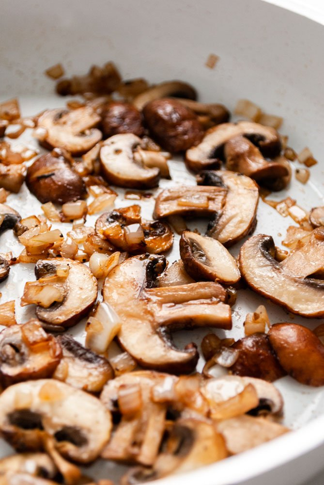 sautéing mushrooms and shallots in a skillet