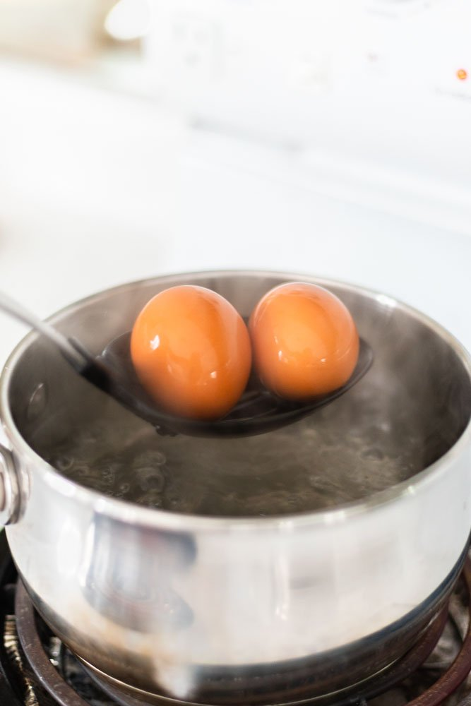 Lowering eggs into a pot of boiling water with a spoon.