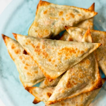 A top down view of a plate of baked samosas.