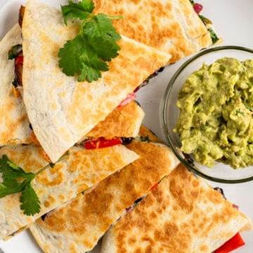 Black bean quesadillas on a plate with guacamole.