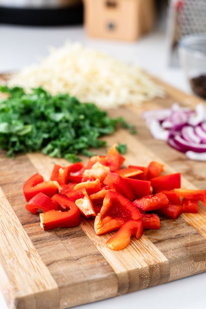chopped red pepper, onion and kale on a cutting board.