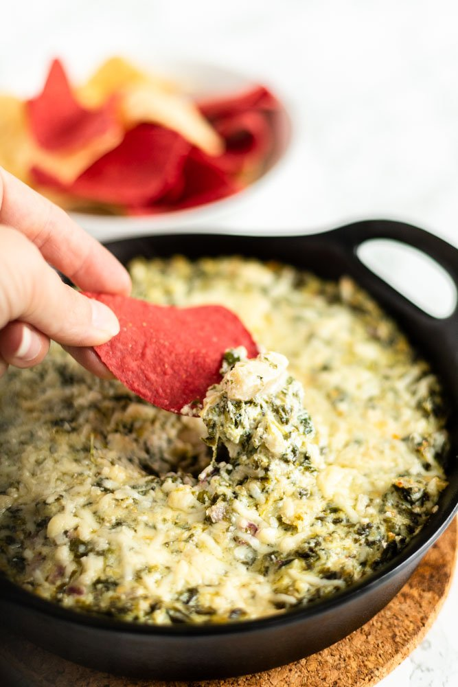 dipping a tortilla chip into fresh baked spinach artichoke dip