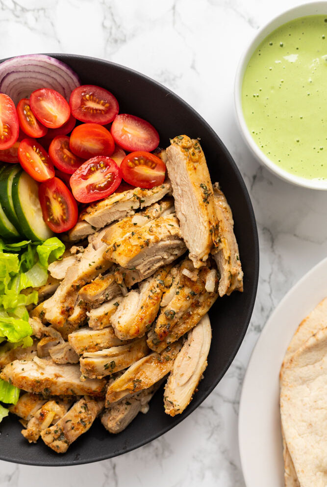 chicken shawarma in a bowl along with toppings and pita bread