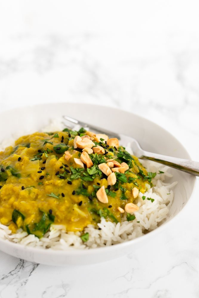 a bowl of red lentil curry topped with cilantro, chopped peanuts and sesame seeds