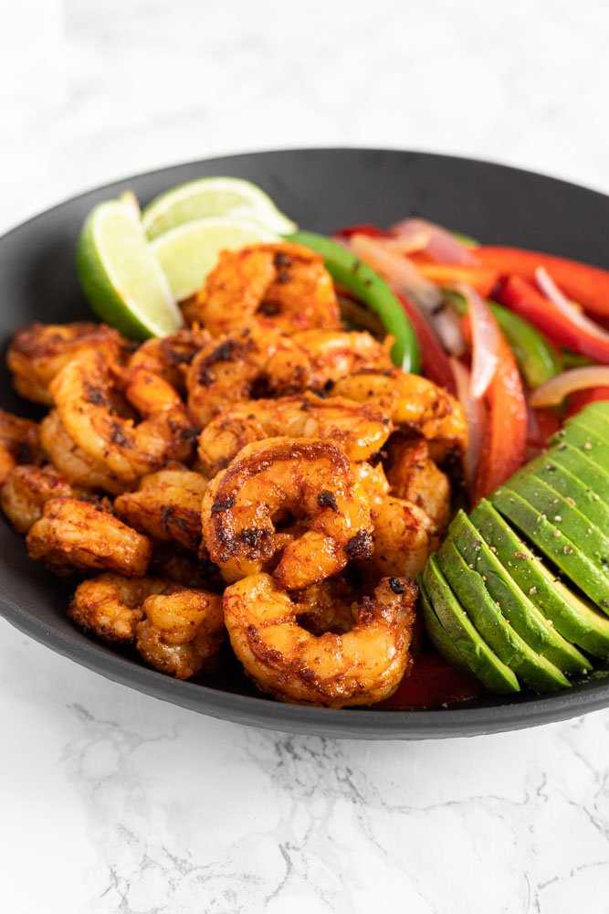 shrimp fajitas in a bowl with sliced avocado and lime
