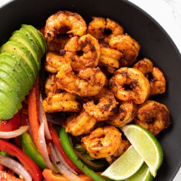 shrimp fajitas in a dish with lime and avocado