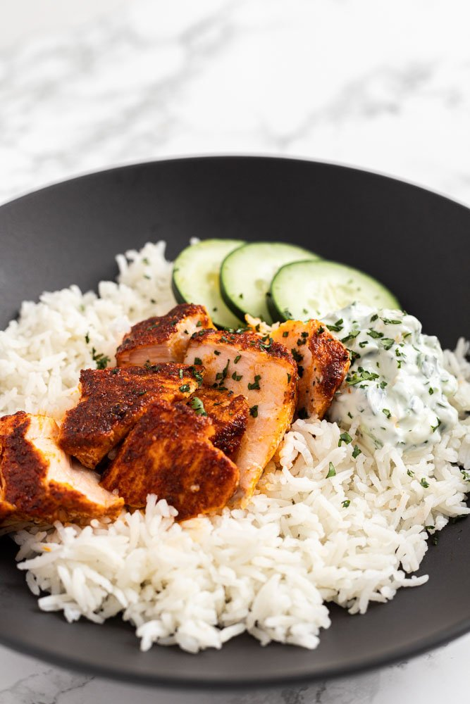 tandoori salmon with raita, rice and cucumber in a bowl