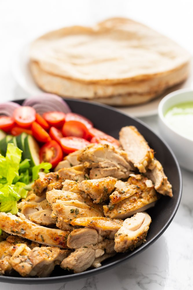 A side view of chicken shawarma in a bowl with pita and toppings.