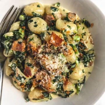a bowl of creamy kale gnocchi with bacon and onions