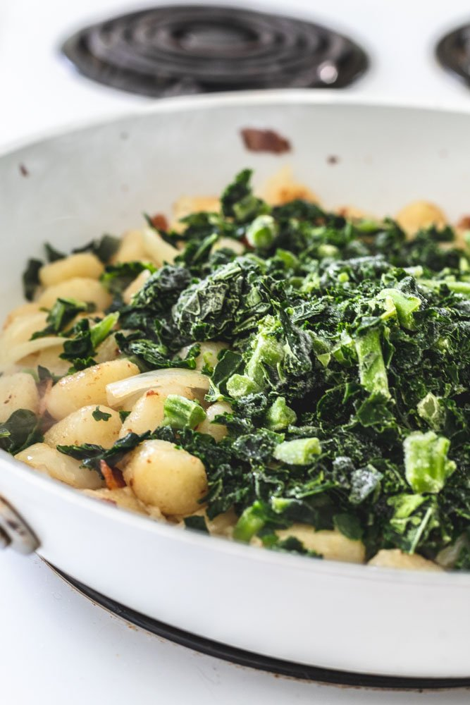 Bacon, onions, gnocchi and kale cooking in a skillet.