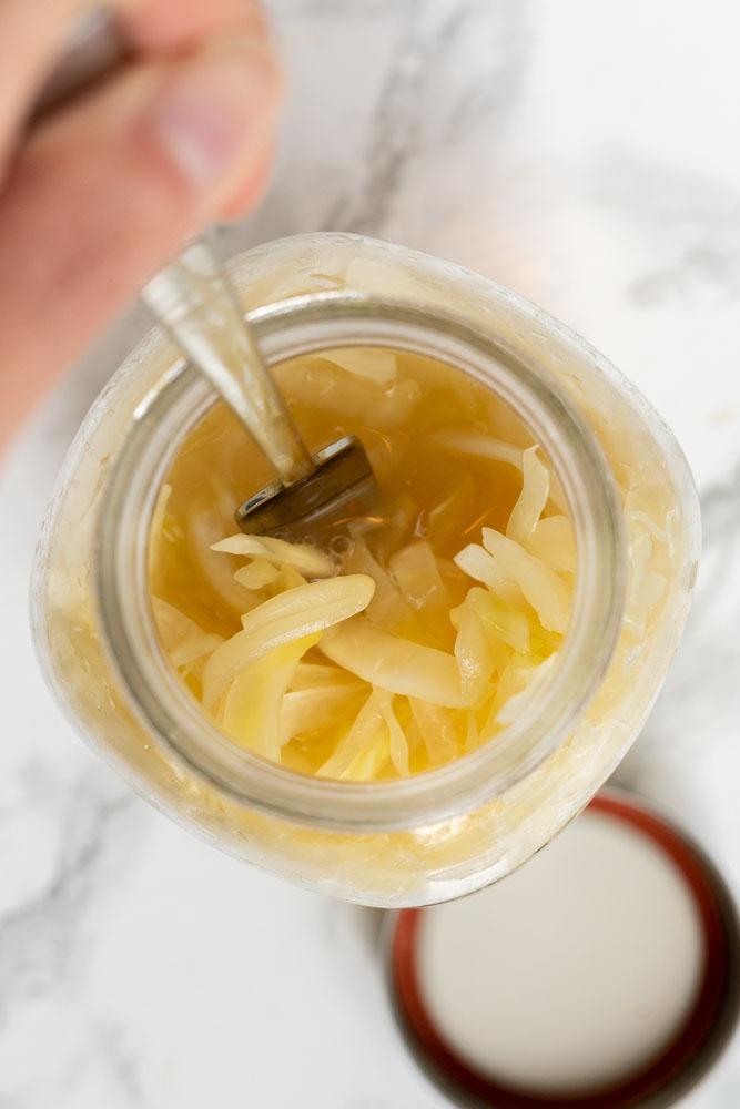 A fork reaching into a jar of sauerkraut.