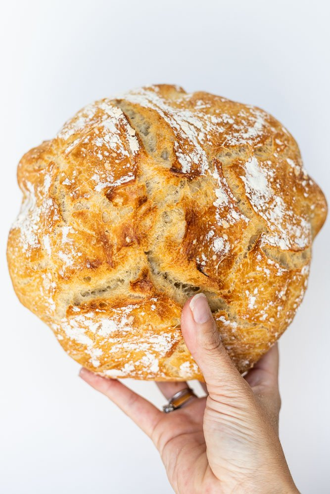 A hand holding up a loaf of no knead bread.