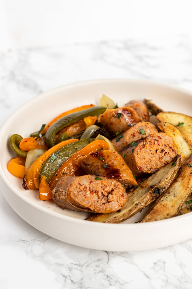 Italian sausage and peppers sheet pan dinner on a plate.