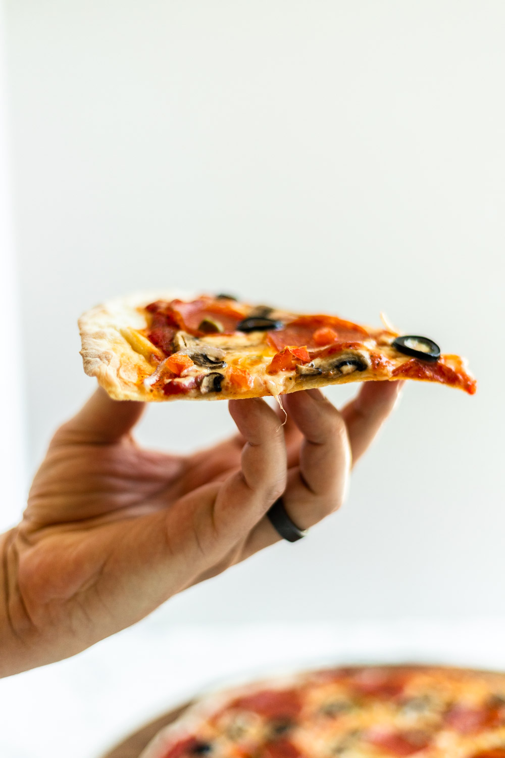 A hand holding a slice of thin crust pizza up.