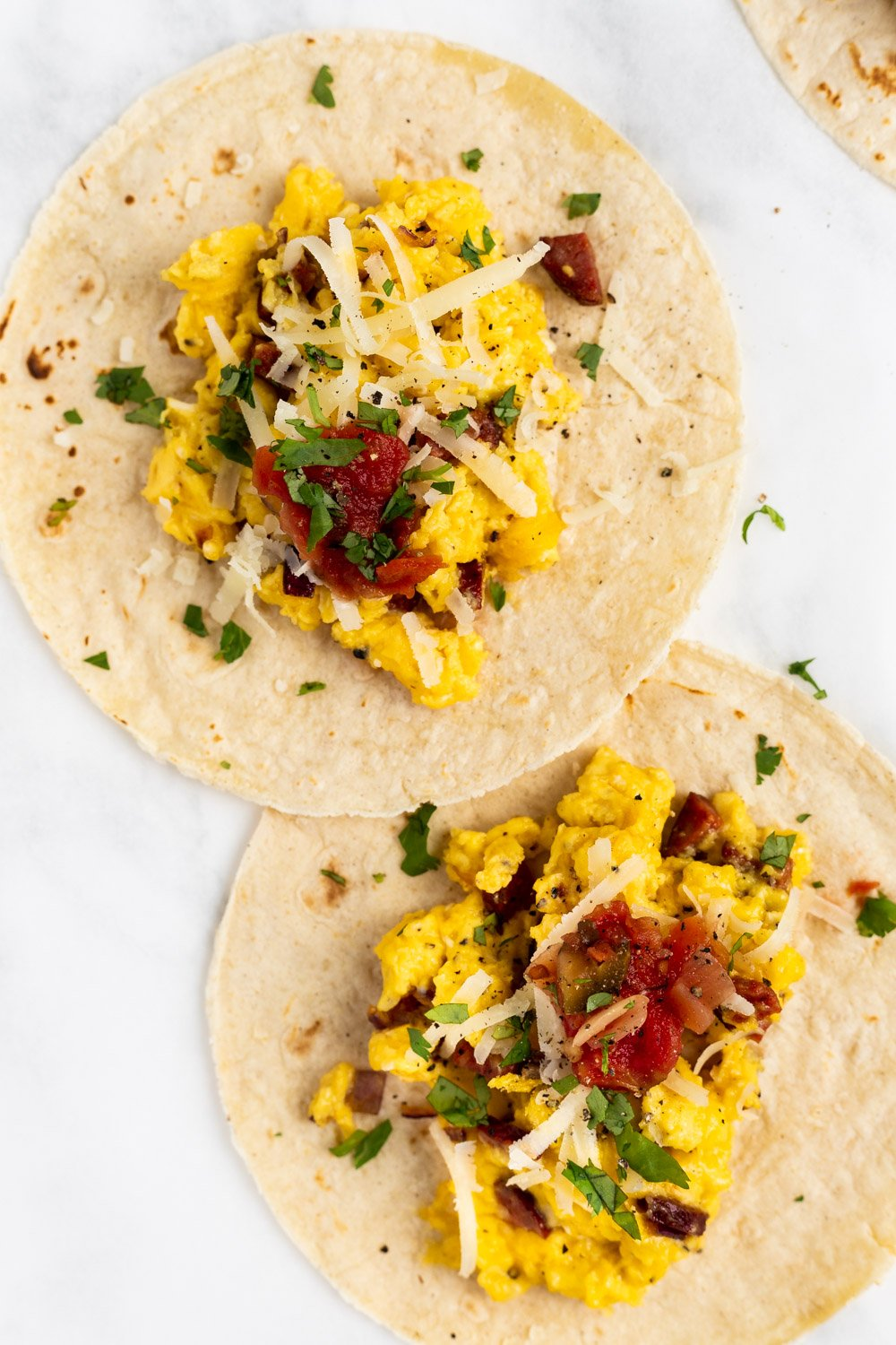 A top down view of two chorizo breakfast tacos on parchment paper.