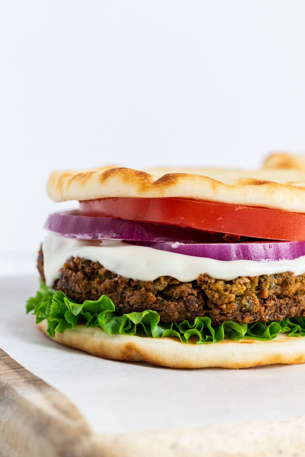 A close up view of a falafel burger with lettuce, tomato and onion.