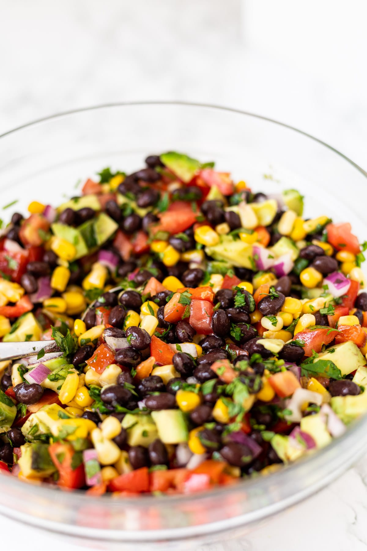 a side view of a bowl of black bean and corn salad with a spoon in it