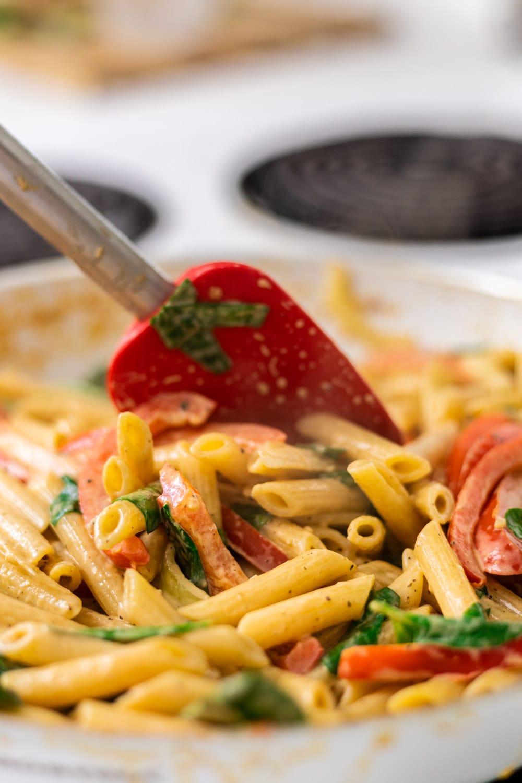 sitrring cajun shrimp pasta in a skillet