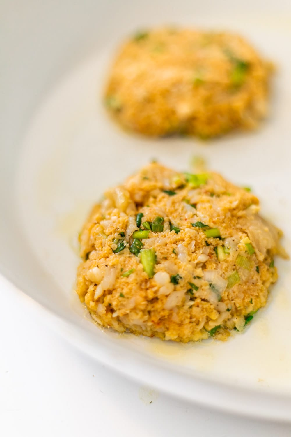 thai fish cakes cooking in a skillet