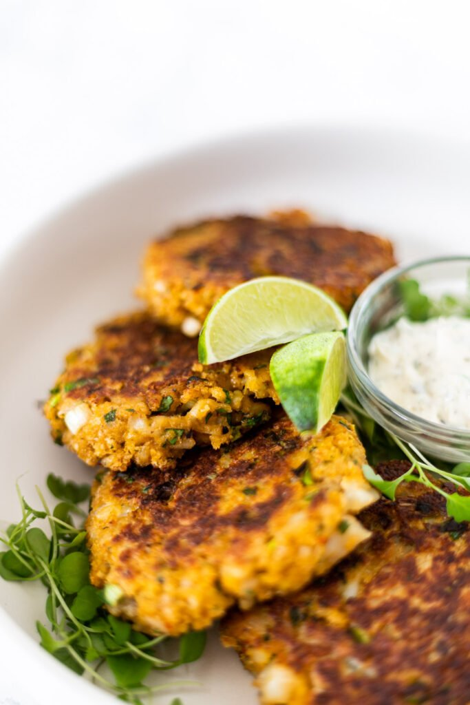 a sideview of Thai fish cakes on a plate with tartar sauce.