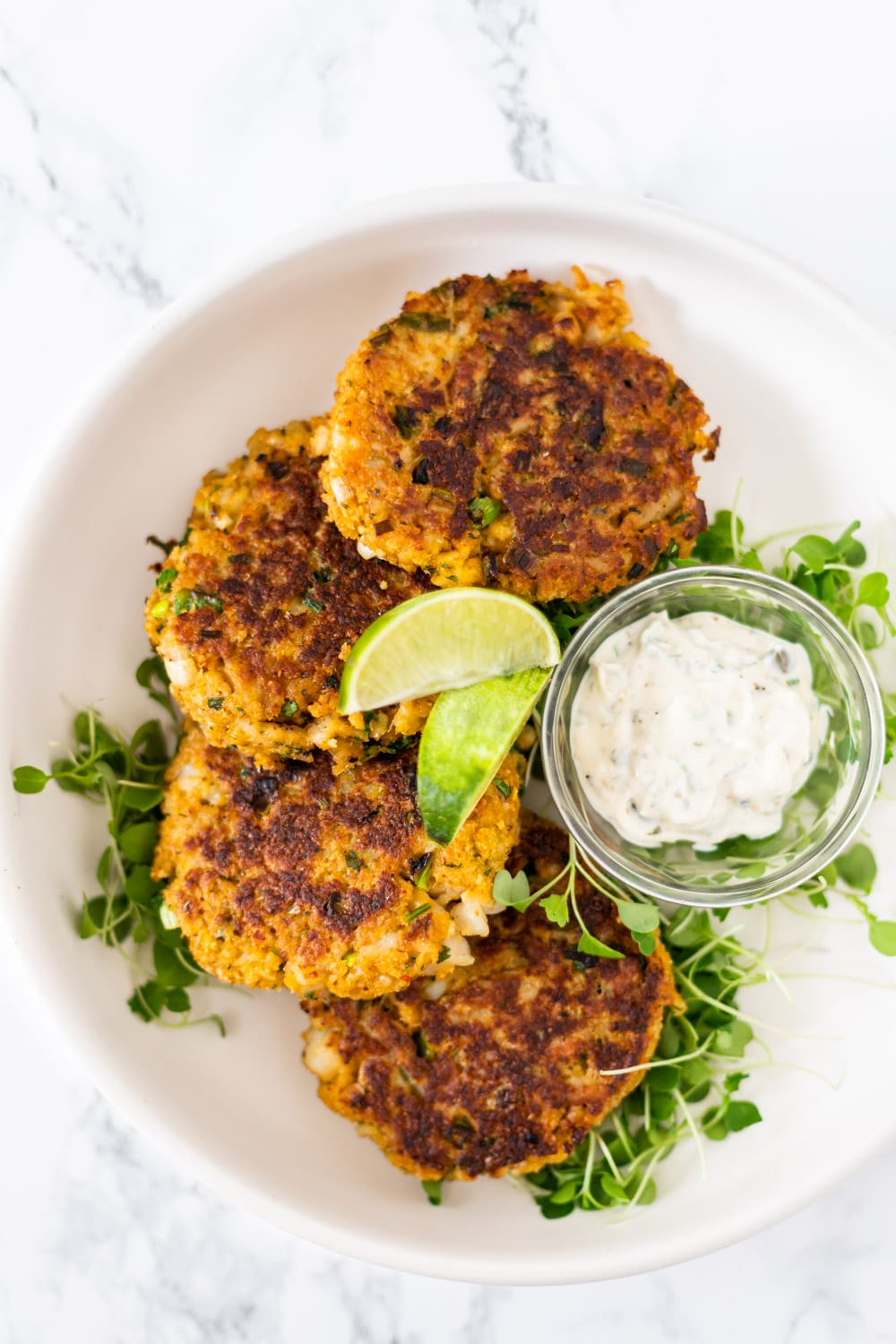 A top down view of Thai fish cakes on a plate with tartar sauce.