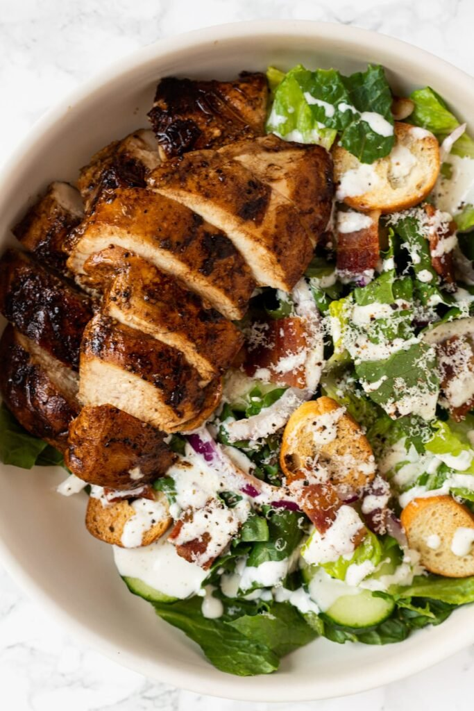 A top down view of a plate of balsamic chicken caesar salad.