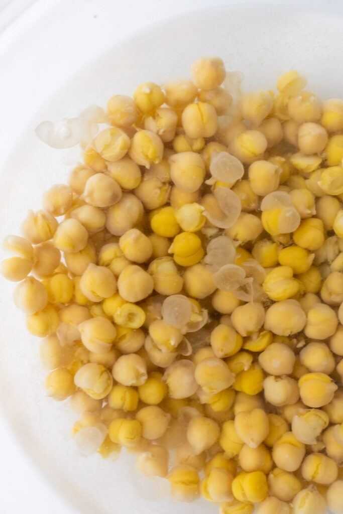 Cooked chickpeas in a bowl of water with skins floating in it.