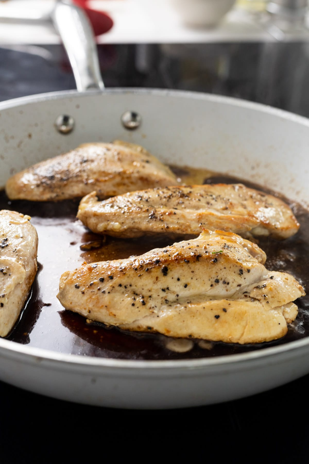 Chicken breasts cooking in a skillet with balsamic vinegar.
