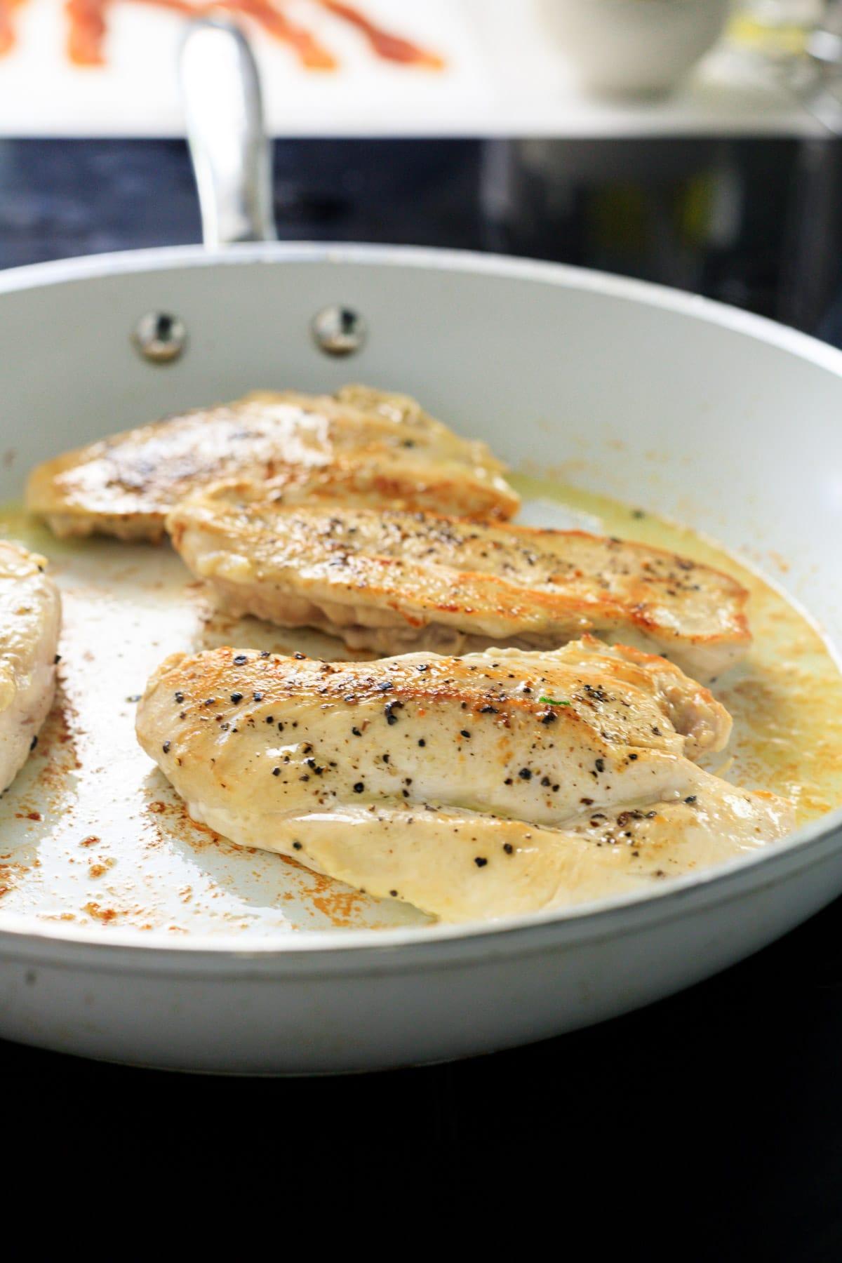 Seasoned chicken breasts frying in a skillet.