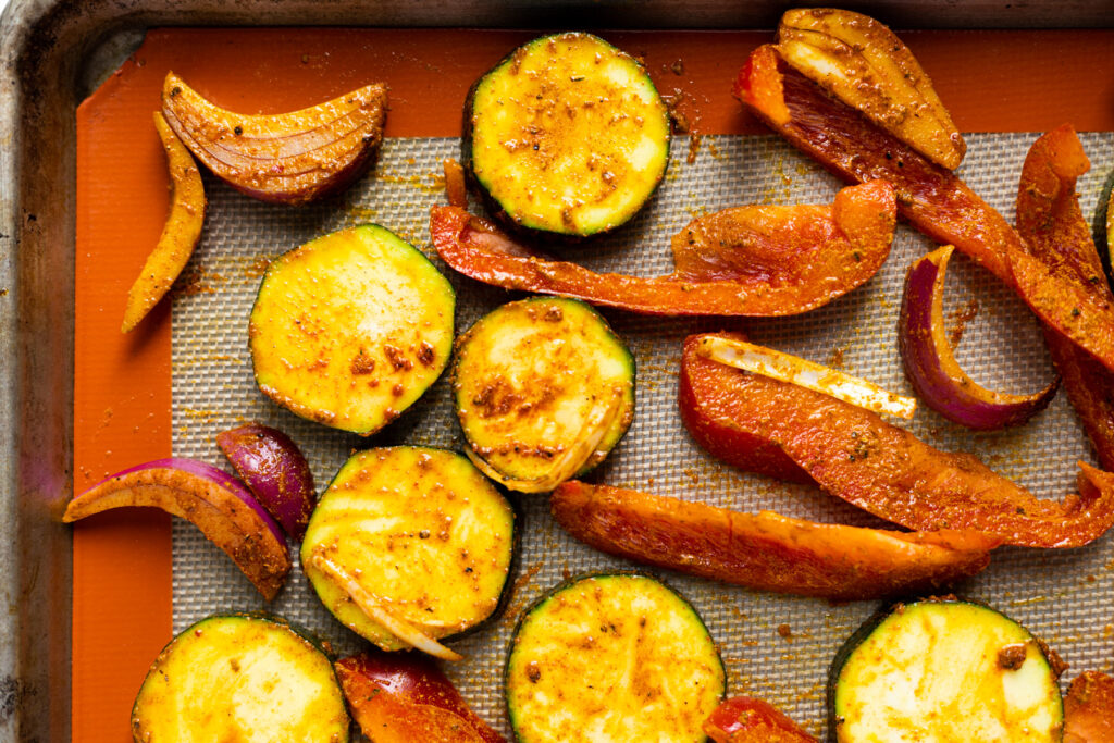 Spiced veggies laid out on a baking sheet.